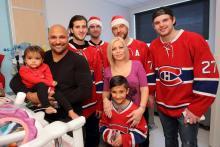 Mila (gauche) et son frère Lohan (centre) sourient avec maman, papa et les joueurs des Canadiens de Montréal.