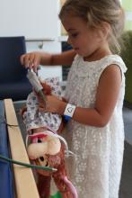 Tazia s'assure de bien relier son ourson à l'appareil de saturation en oxygène qui surveillera son état en continu pendant l'opération.